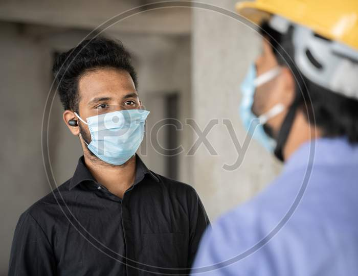 Shoulder Shot, Construction Worker And Engineer At Site Talking By Wearing Medical Mask With Social Distance - Concept Of Business, Industry Reopen And Covid-19 Safety Measures At Workplace.