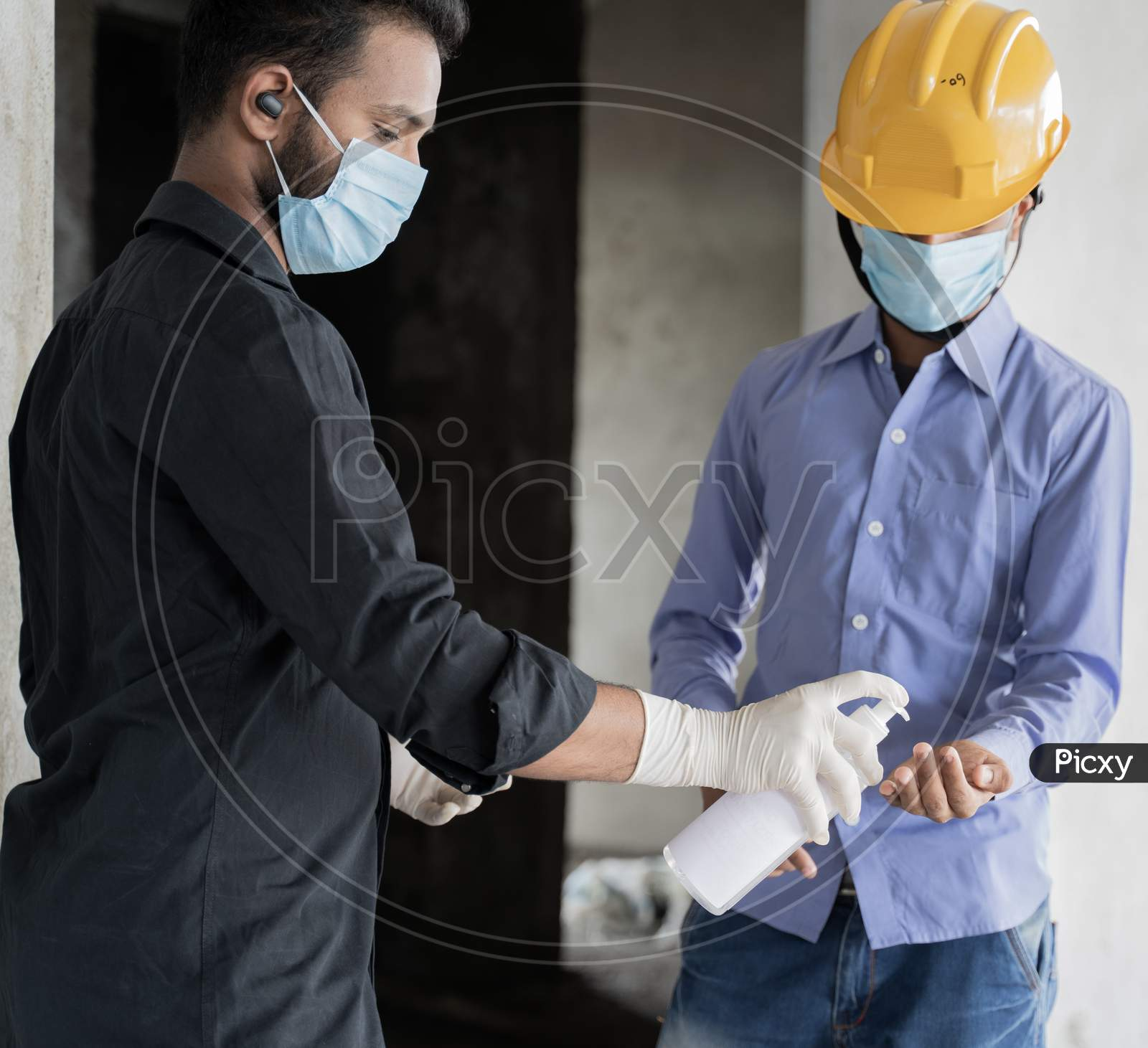 Poeple At Construction Site Using Hand Sanitizer Before Entering To Work Place As Covid-19 Or Coronavirus Safety Measures