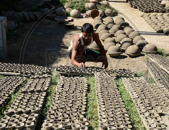 A  Potter arranging  earthen lamps being sun dried for upcoming Diwali festival at Rupohi village in Nagaon District of Assam on Nov 10,2020.