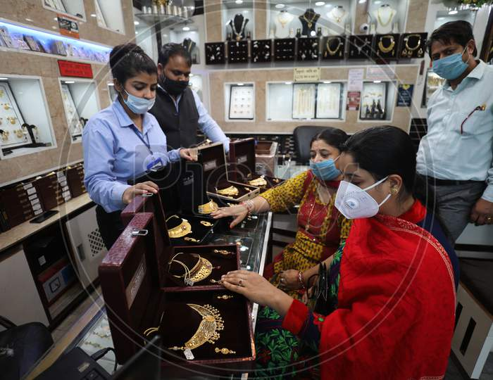 People buy gold ornaments at a jewellery showroom on the auspicious occasion of Dhanteras, in Jammu ,12,November,2020.