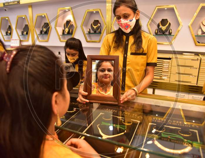 :A woman tries a gold ornaments  at a jewellery showroom during Dhanteras in Nagaon district, in the northeastern state of Assam on Nov 12,2020