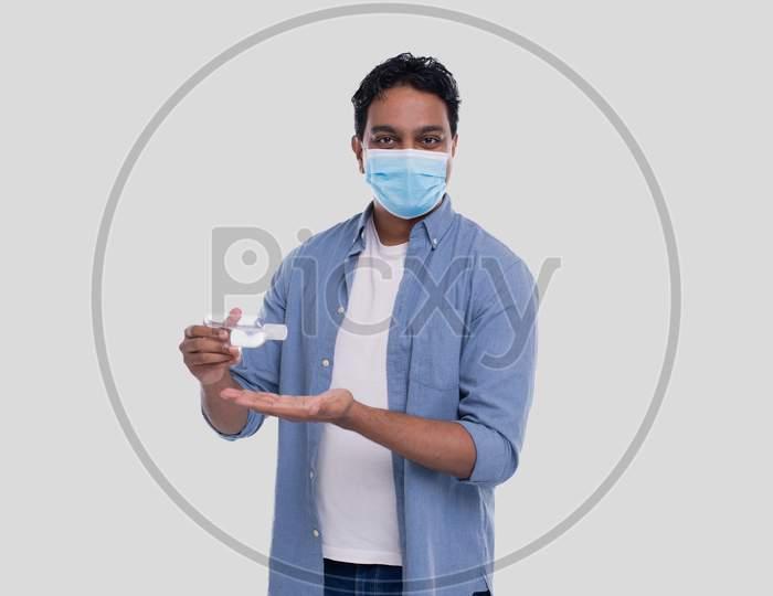Indian Man Wearing Medical Mask Using Hand Sanitizer. Man Using Hands Antiseptic