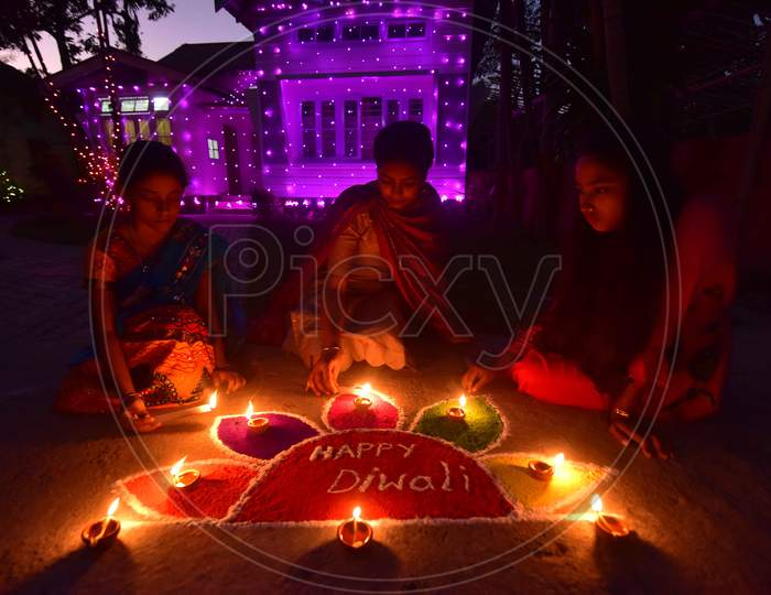 """Girls pose after lighting oil lamps around a """"Rangoli"""", a traditional pattern made from coloured powders and flower petals outside their home  to celebrate Diwali, the Hindu festival of lights, in Nagaon District of Assam,india  on Nov 14,2020."""
