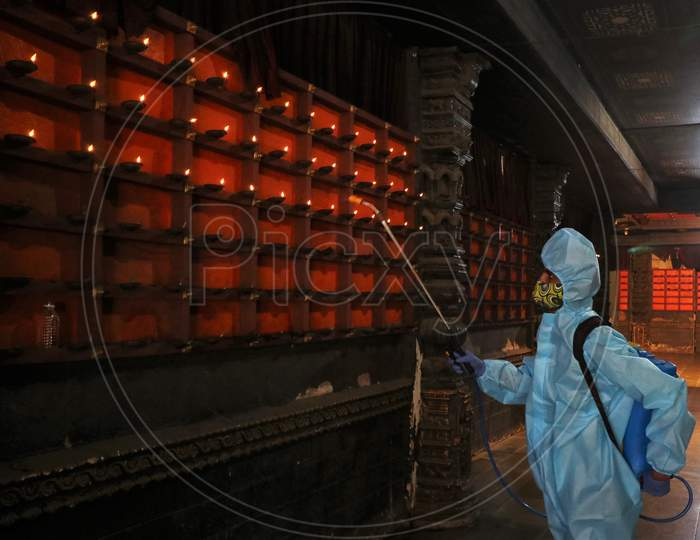A man in personal protective equipment (PPE) sanitizes a temple before they reopen for the public amid the spread of the coronavirus disease (COVID-19) in Mumbai, India on November 15, 2020.