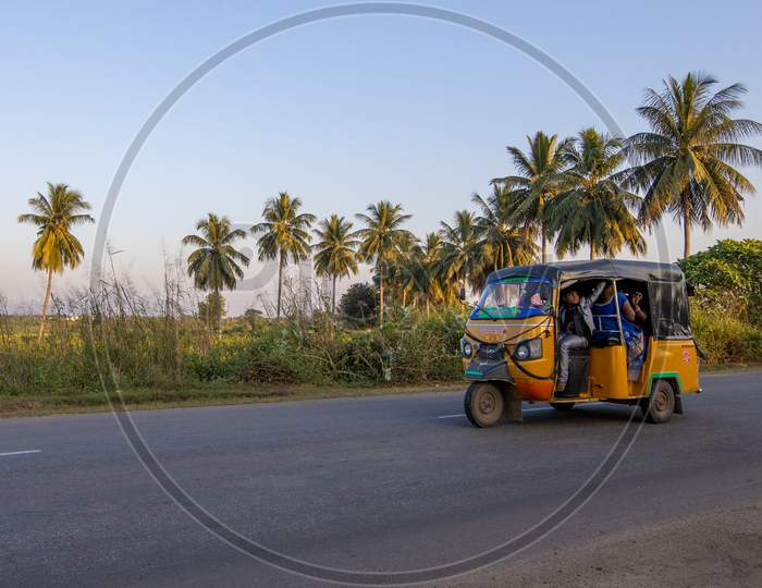 Auto rickshaw travelling with passengers on Indian State Highway
