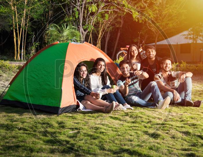 Group Of Asian Indian Young Friends Relaxing Outside Tents On Camping Holiday