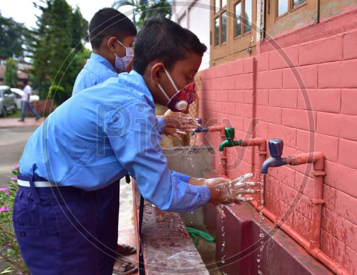 Students wash their hands  at a  School after schools re-opened following a gap of more then seven months due to coronavirus pandemic in Nagaon District of Assam on Nov 2,2020.