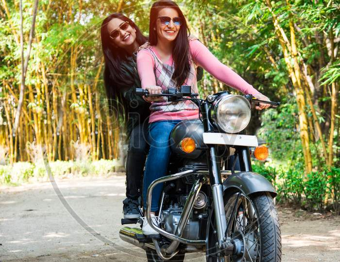 Happy Asian Indian Young Woman Or Female Friends Riding On Motorcycle Or Motorbike