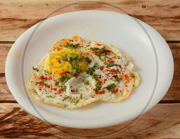 Indian Style Tasty And Healthy Egg Half Fried Omelet On A Wooden Rustic Background. Selective Focus