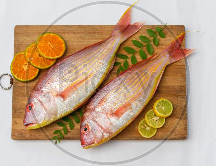 Top View Of View Of Fresh Pink Perch (Thread Finned Bream) Decorated With Lemon Slice,Orange Slice And Curry Leaves On A Wooden Pad,White Background,Selective Focus.