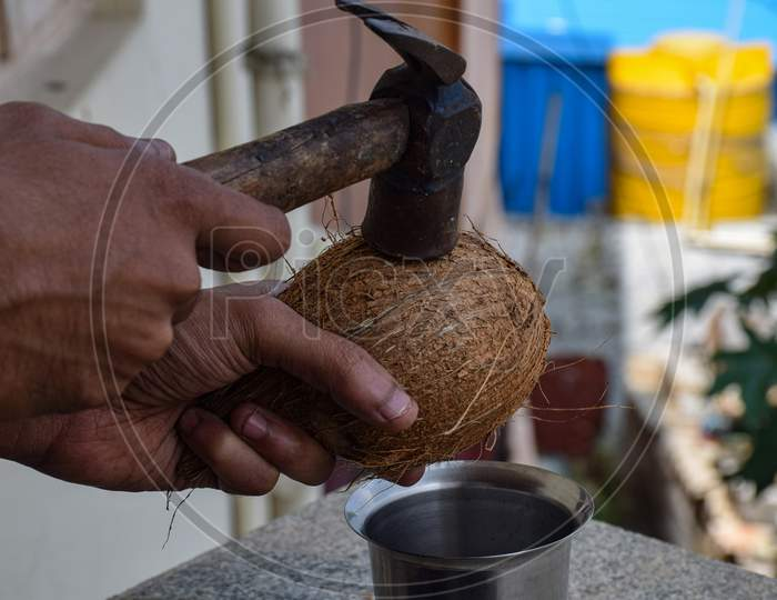 Picture Of A Man Breaking Raw Coconut From Hammer
