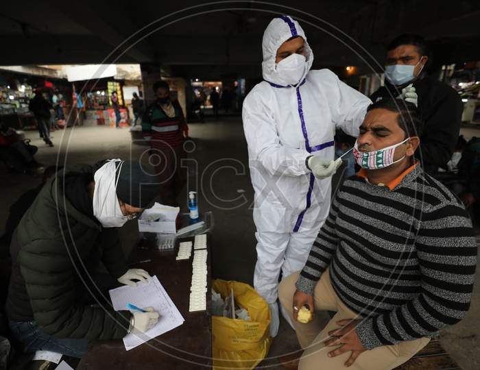 Health worker collects a swab sample for COVID-19 test at Gernal Bus stand in Jammu ,25 November,2020.