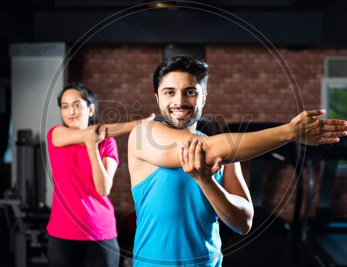 Indian Asian Young Couple Stretching In Gym Post Exercise
