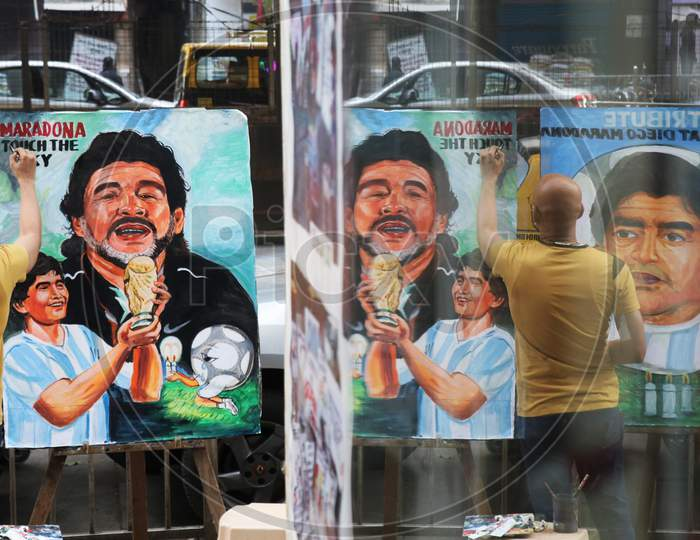 An artist paints a tribute to late Argentine soccer legend Diego Maradona, on a street in Mumbai, India in November, 2020.