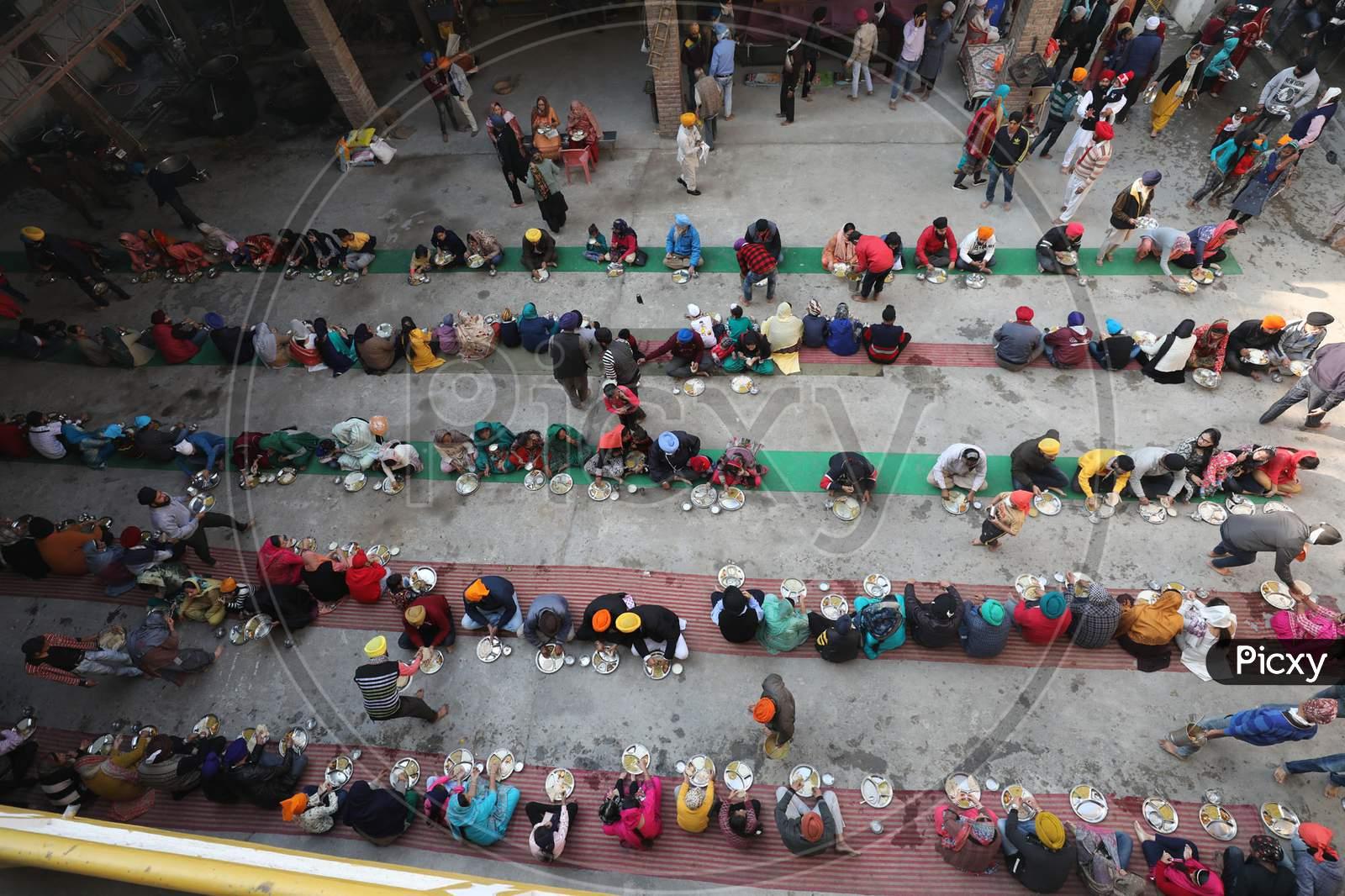 Sikh devotees, eat a meal from a community kitchen during celebrations to mark the birth anniversary of the first Sikh Guru, Guru Nanak Dev, at a Gurudwara, or Sikh temple, in Jammu,30 November,2020.