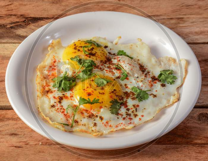 Indian Style Tasty And Healthy Double Egg Half Fried Omelet On A Wooden Rustic Background. Selective Focus