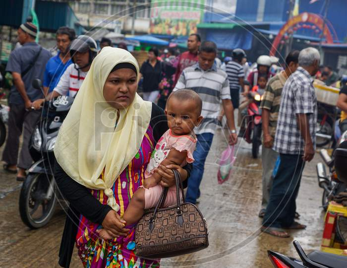 Muslim Girl Bring Her Child Shopping At The Market
