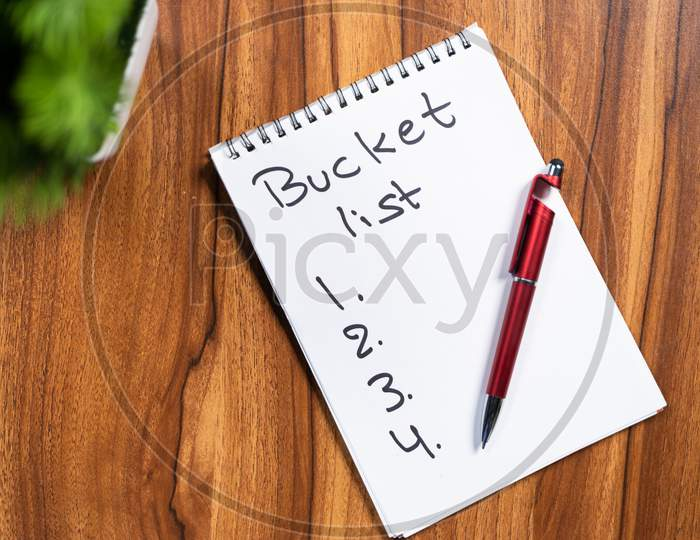 Pen And Book With Written Bucket List On Note Book For 2021 New Year.