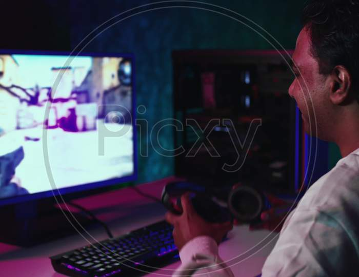 Indian Man Starts To Play Pc Game. Man Puts On Headphones And Plays Shooting Game. Gamer At Home Playing Games. Indian Man Playing Games. Shot On Red