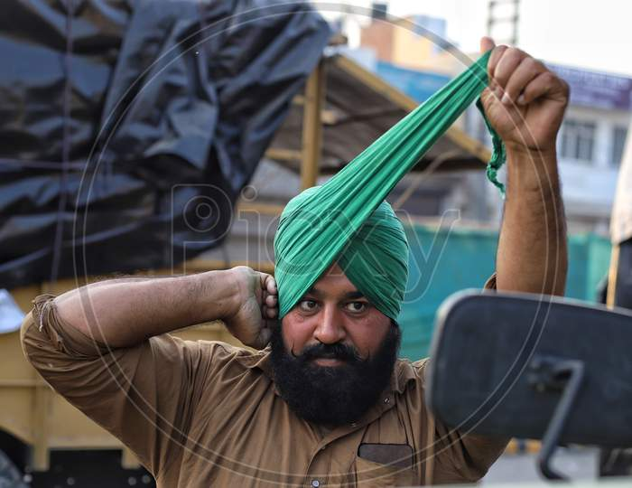 A Sikh farmer ties his turban during a farmers protest at Singhu Border. Thousands of farmers are protesting against  new farm laws at various entry points of New Delhi, India.