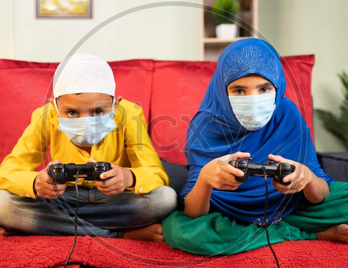 Two Muslim Kids With Medical Face Mask Busy Playing Video Game Using Gamepad At Home - Concept Of Kids On Game During Coronavirus Covid-19 Lockdown.