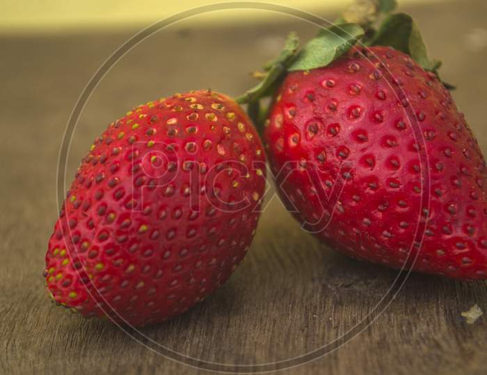 Two Red Strawberries On A Wooden Surface
