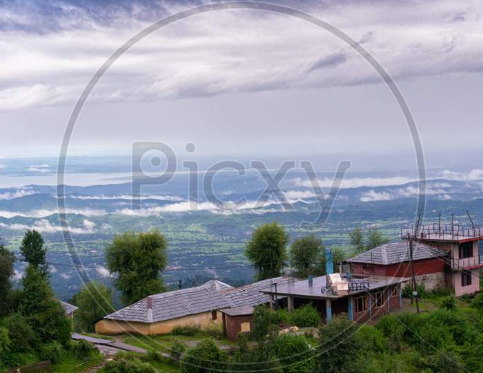 Building Perched On The Edge Of A Mountain With Trees All Around Looking Over A Beautiful Vista Landscape Of A Valley Covered In Clouds At Dawn Shot In Mcleodganj Of Dharamshala Valley In Himachal Pradesh In India A Popular Tourist And Homestay Destination