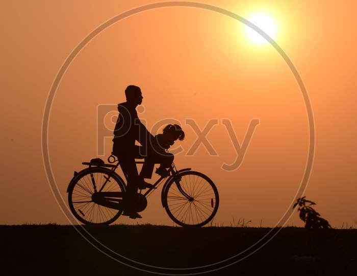 A man rides a bicycle during  the last sunset of the year in  Assam on Dec 31,2020