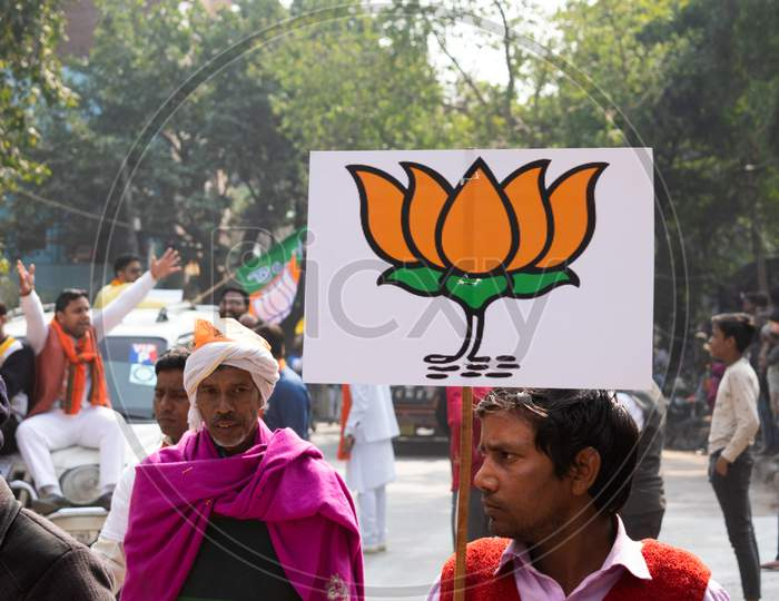 Men having electoral sign for BJP during Bharatiya Janata Party campaign for Delhi Assembly Election 2020