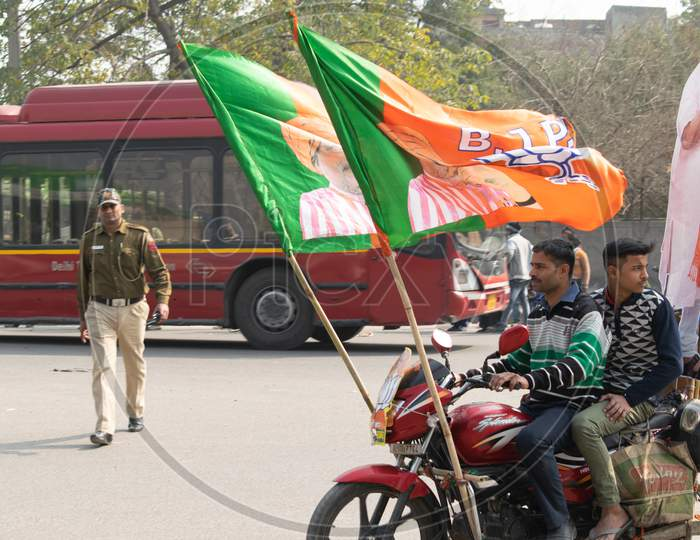 Men riding bike with BJP Flags during Bharatiya Janata Party campaign for Delhi Assembly Election 2020