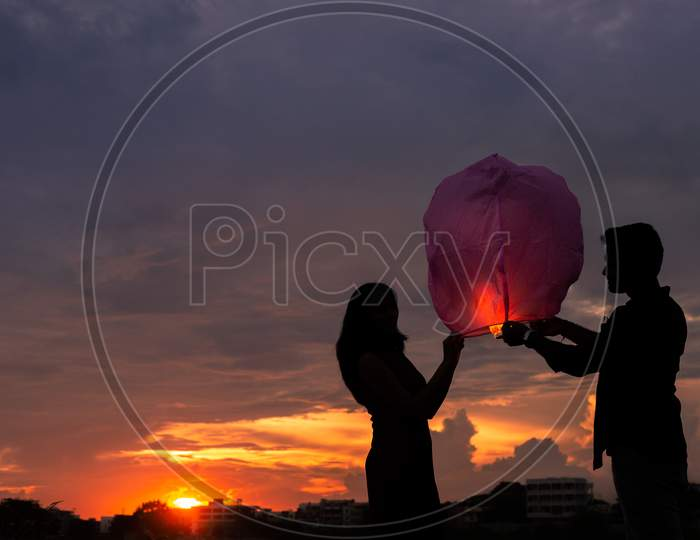 Silhouette of Indian couple holding lantern