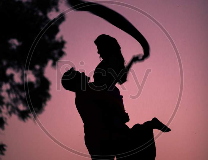Silhouette of Indian Man holding his wife with hands during photoshoot