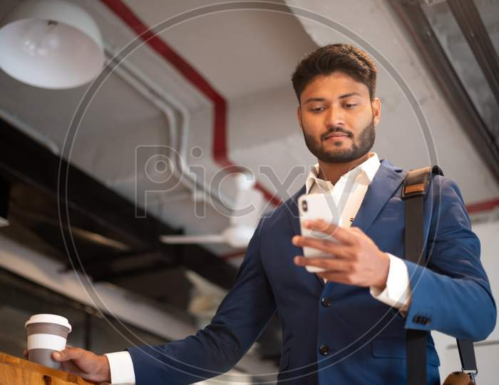 Indian Young Businessman Holding Coffee Cup at An Office
