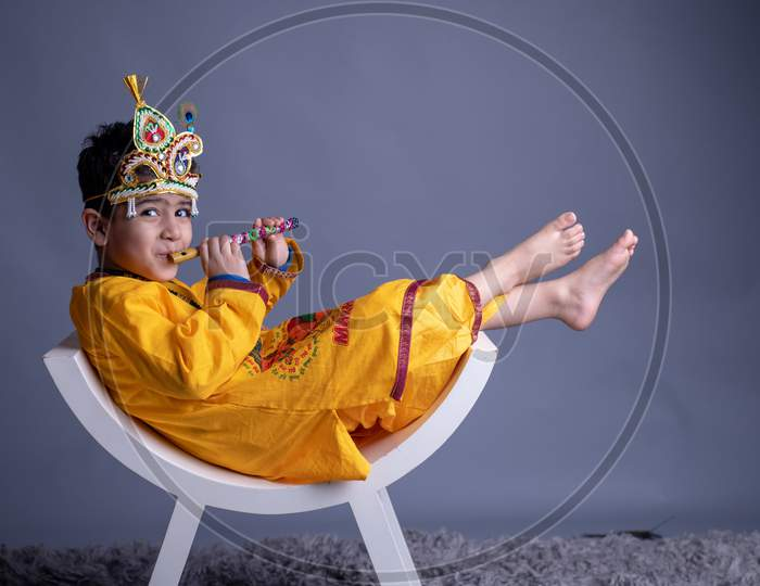 Young Indian Boy Dressed like Lord Sri Krishna And Posing Over an Gray Background