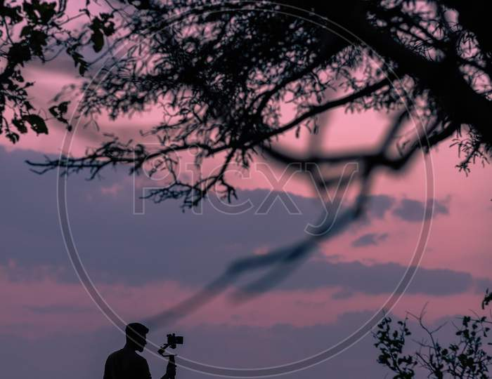 Silhouette Of A Photographer Holding a Camera Over Sunset Sky In Background