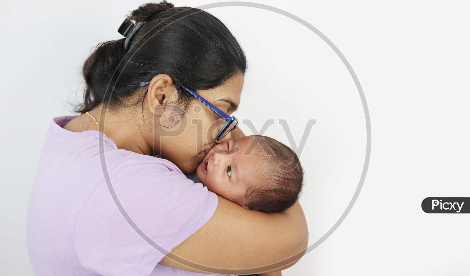 A Young Mother In Spectacles Kissing Her Infant Baby Boy In Her Lap In Solid Grey Background With Space For Text. Mothers Day Concept Photo.