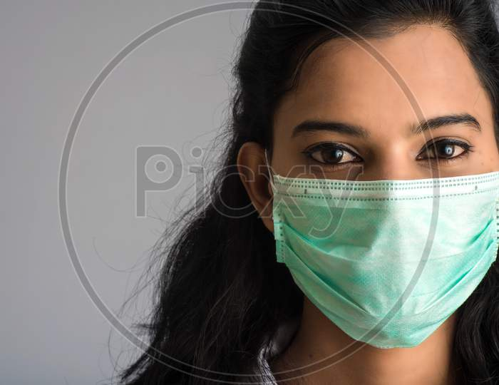 Closeup Portrait Of A Young Girl Or Woman Doctor Wearing A Medical Or Surgical Mask