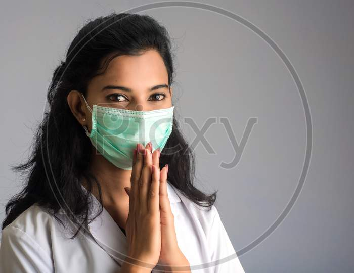 Young Woman Doctor Doing Namaste Because Of Outbreak Of Covid-19. New Greeting To Avoid The Spread Of Coronavirus Instead Of Greeting With A Hug Or Handshake.