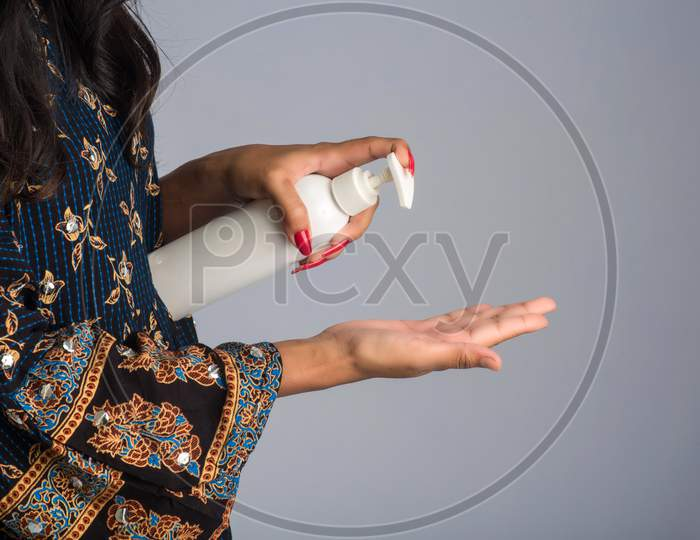 Portrait Of Young Girl Using Or Showing A Sanitizing Gel From A Bottle For Hands Cleaning.