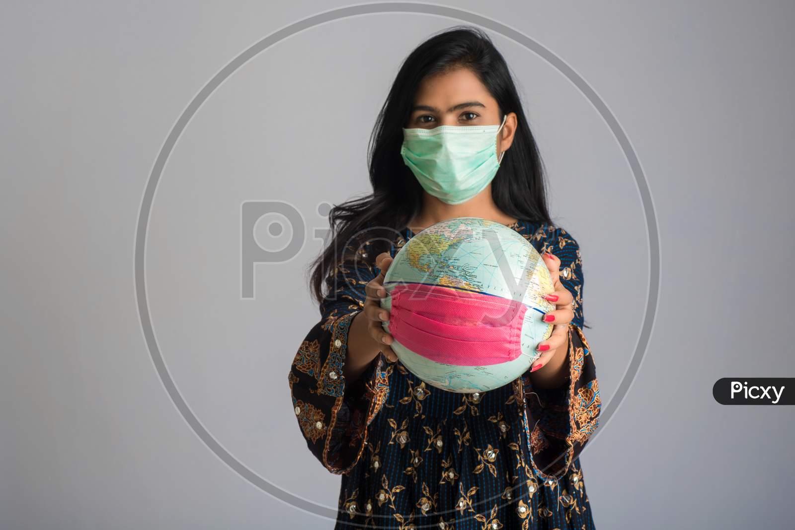 Young Girl Holding World Globe With A Medicine Face Mask. World Epidemic Of Coronavirus Concept.