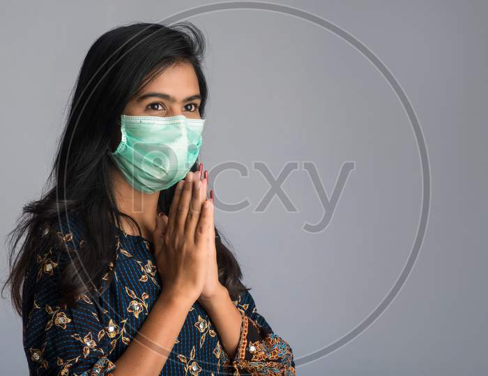Portrait Of A Girl Wearing A Medical Mask Doing Greeting With Namaste Gesture.