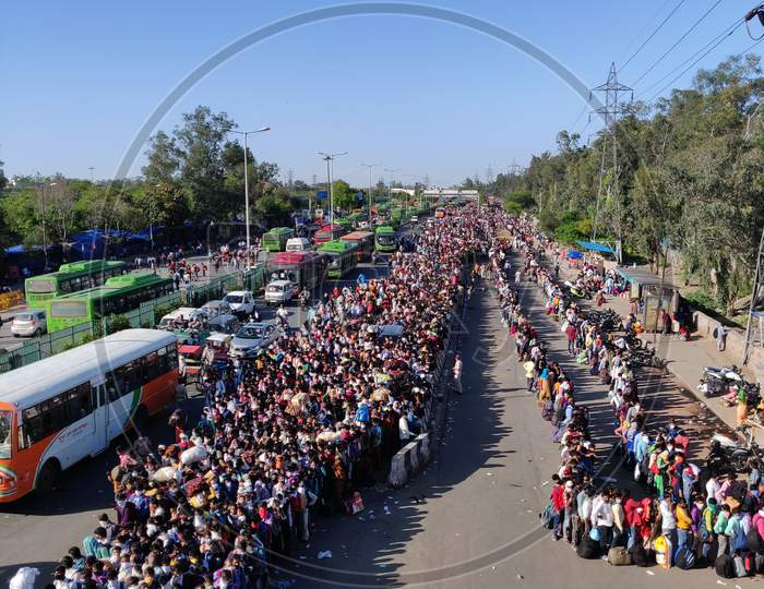 Thousands Of Migrants Lineup Outside the Anand Vihar Bus Terminal Hoping To Catch a Bus Home Amidst National Lockdown Due To COVID-19 Outbreak in India