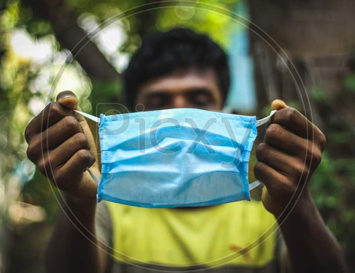 Protection Against Contagious Disease, Coronavirus. Man Wearing Hygienic Mask And Holding On His Hand To Prevent Infection, Airborne Respiratory Illness Such As Flu, 2020. Outdoor Shot Isolated On Nature Background. Asian Young Man Wearing Blue Mask