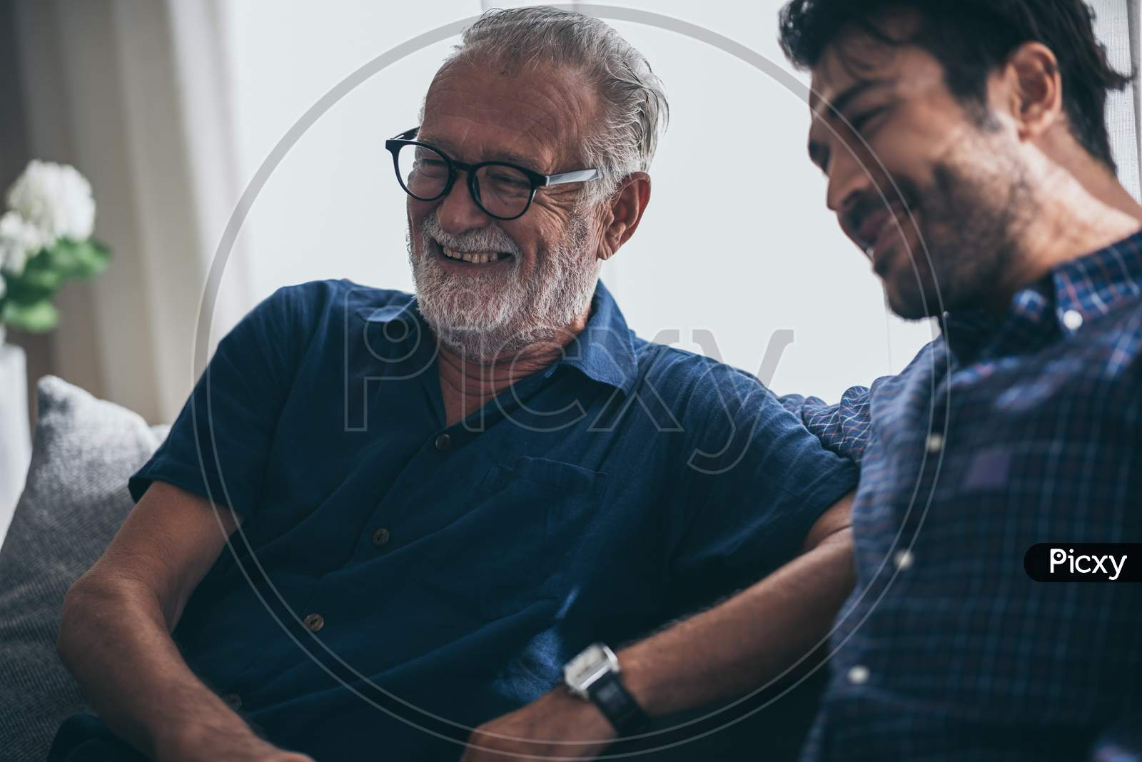 Sweet Bonding. Cheerful Elderly Man Sitting On The Sofa Next To His Adult Son, Hugging Him And Posing Together With Him