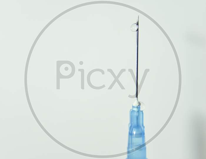 Clear Drop Of The Vaccine On The Top Of The Needle Of Syringe On The White Background