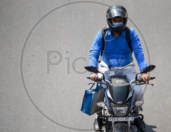 A man wearing the preventive pollution mask on his face as he rides his bike to protect himself from Novel Corona Virus, COVID-19
