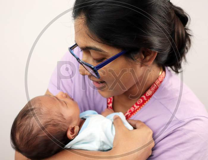 A Mother Cuddling Her Baby Isolated In White Background With Space For Text.