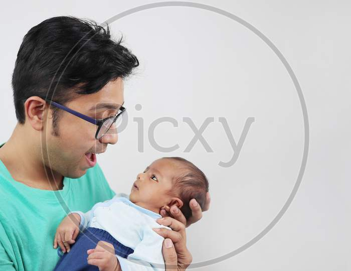 A Father Making Funny Face At His Baby Isolated In White Background With Space For Text.