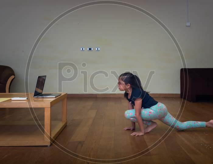 a girl performing yoga and doing meditation as instructed by her teacher through e learning platform