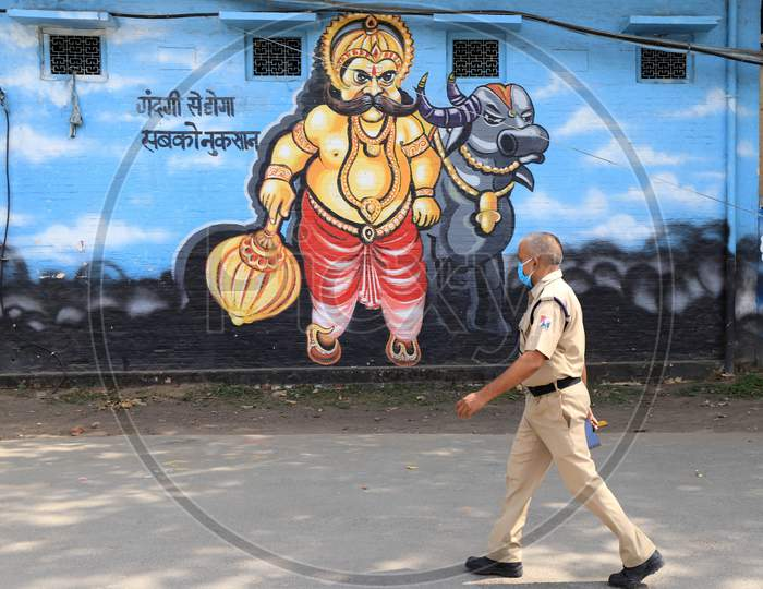 A Rpf Jawan Walk In Front Of Wall Painting Of Yamraj During A Nationwide Lockdown To Slow The Spreading Of The Coronavirus Disease (Covid-19), In Prayagraj, April, 17, 2020.
